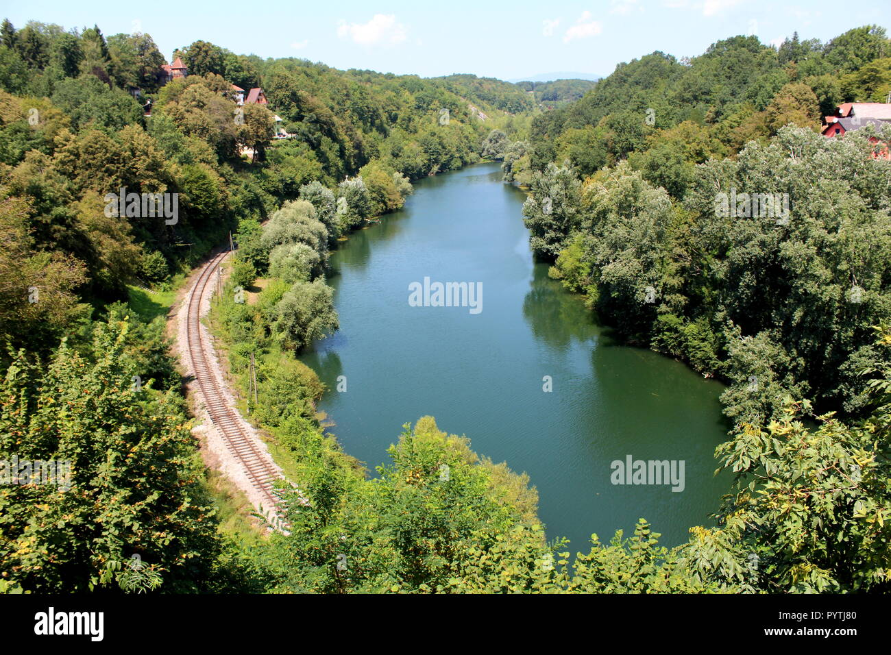 Clear river surrounded with family houses between tall trees, overgrown vegetation and railway tracks with wooden electrical utility poles - Stock Image