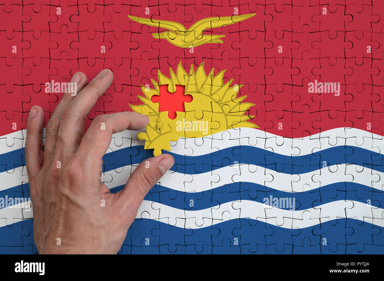 Kiribati flag  is depicted on a puzzle, which the man's hand completes to fold. - Stock Image