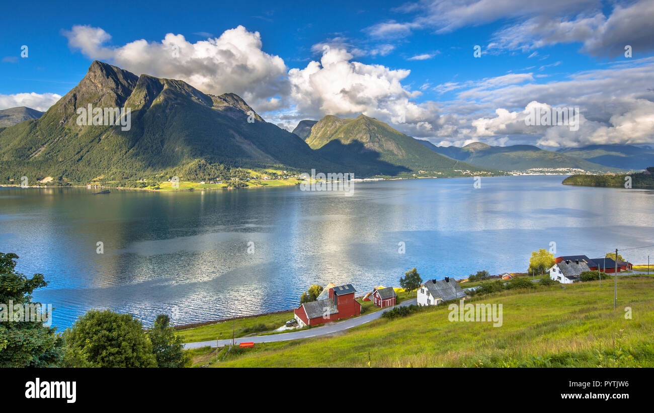 Norwegian fjord landscape on sunny day in august with houses and villages near Volda - Stock Image