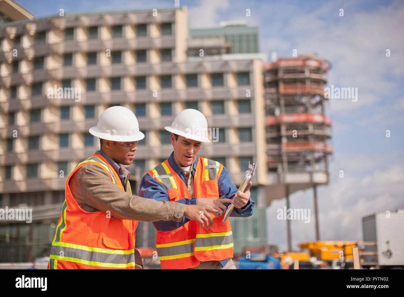 Two engineers in high visibility vests and hardhats discuss building plans on a construction site. - Stock Image