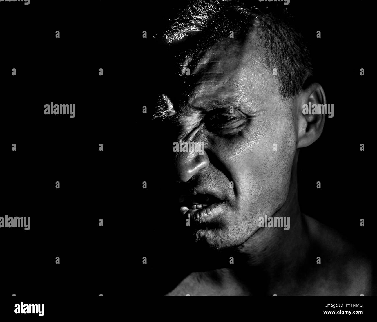 Stylish portrait of adult caucasian man with very angry face and who seems like maniac or devil. He screams at someone. Black and white shot, low-key  - Stock Image