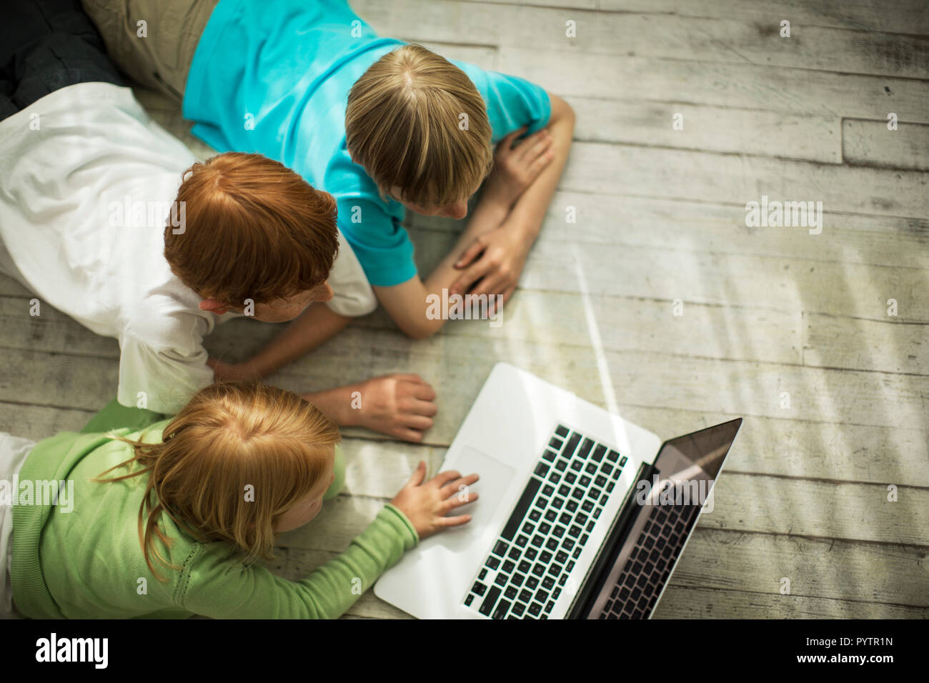 Happy siblings playing with a laptop computer. Stock Photo
