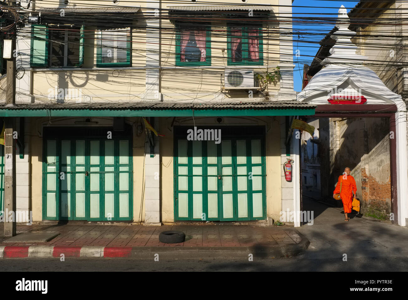 A Buddhist monk leaving the grounds of Wat Suthat, Bangkok, Thailand, for Dinso Rd., lined with old Chinese shophouses - Stock Image