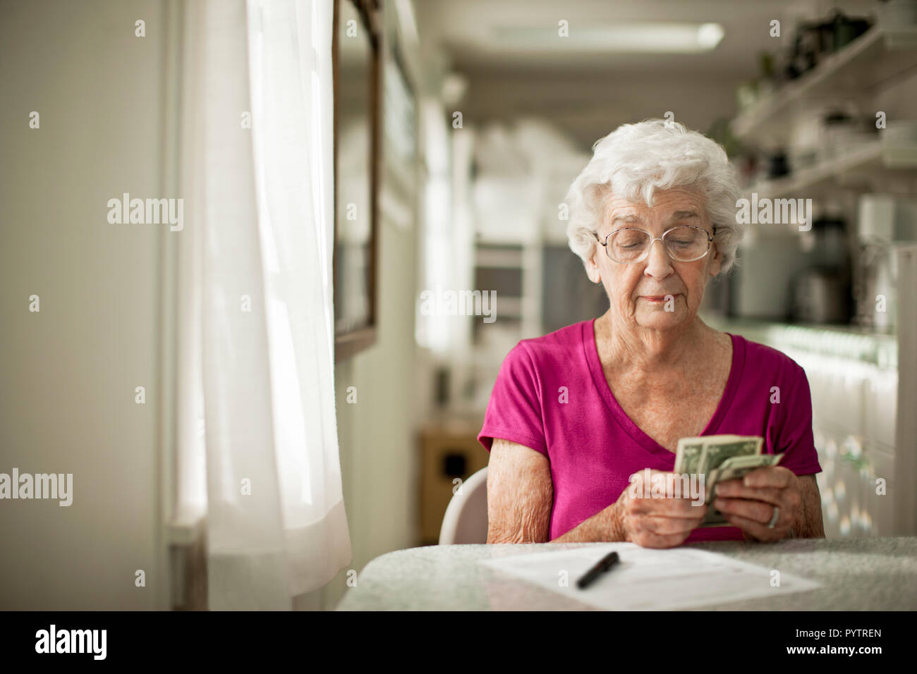 Anxious elderly woman sorts through her money to see if she has enough to pay the bill in front of her. Stock Photo