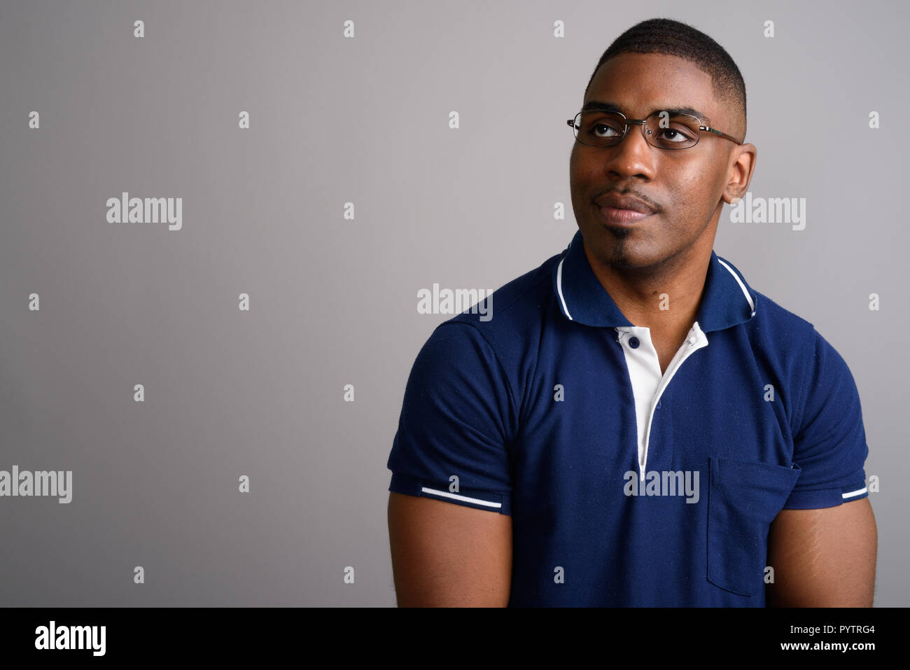 8c733b427 Young handsome African man wearing blue polo shirt against gray ...