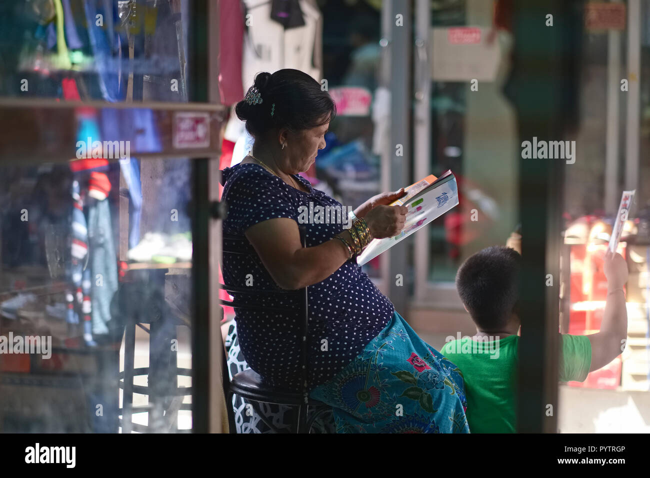 An ethnic Nepalese migrant worker from Myanmar (Burma) in Bangkok, Thailand, perusing a magazine - Stock Image