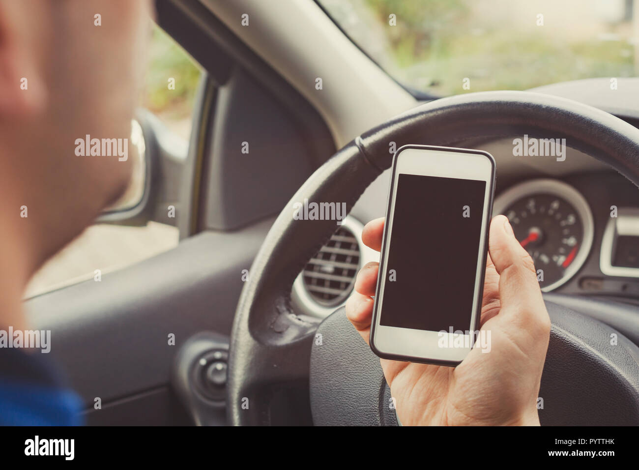 Man using smartphone in car, driver holding mobile phone with empty blank screen. - Stock Image