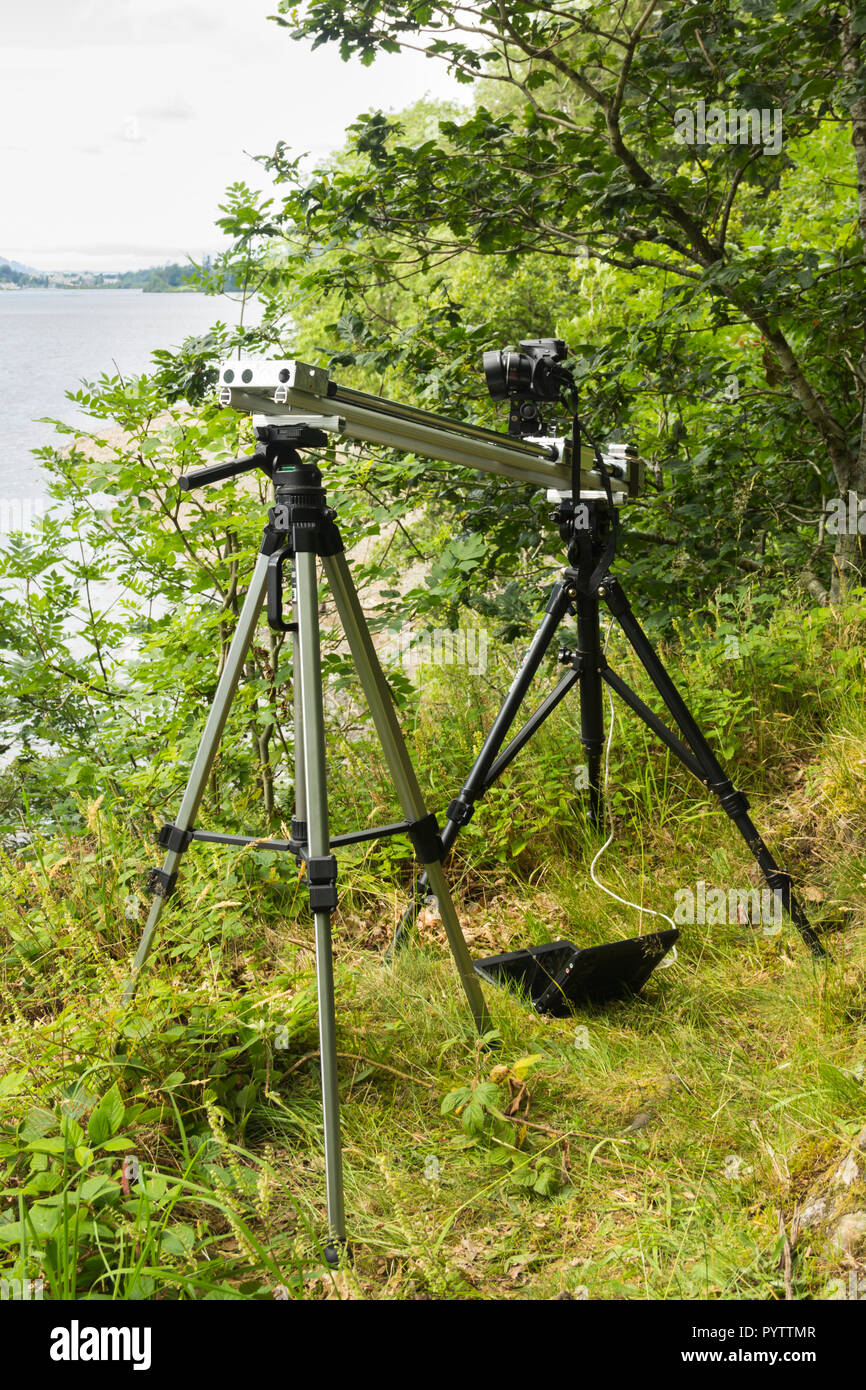 Timelapse setup. A Canon Powershot camera is mounted on a home-made motorised camera slider, on the banks of Derwentwater for timelapse filming. Stock Photo