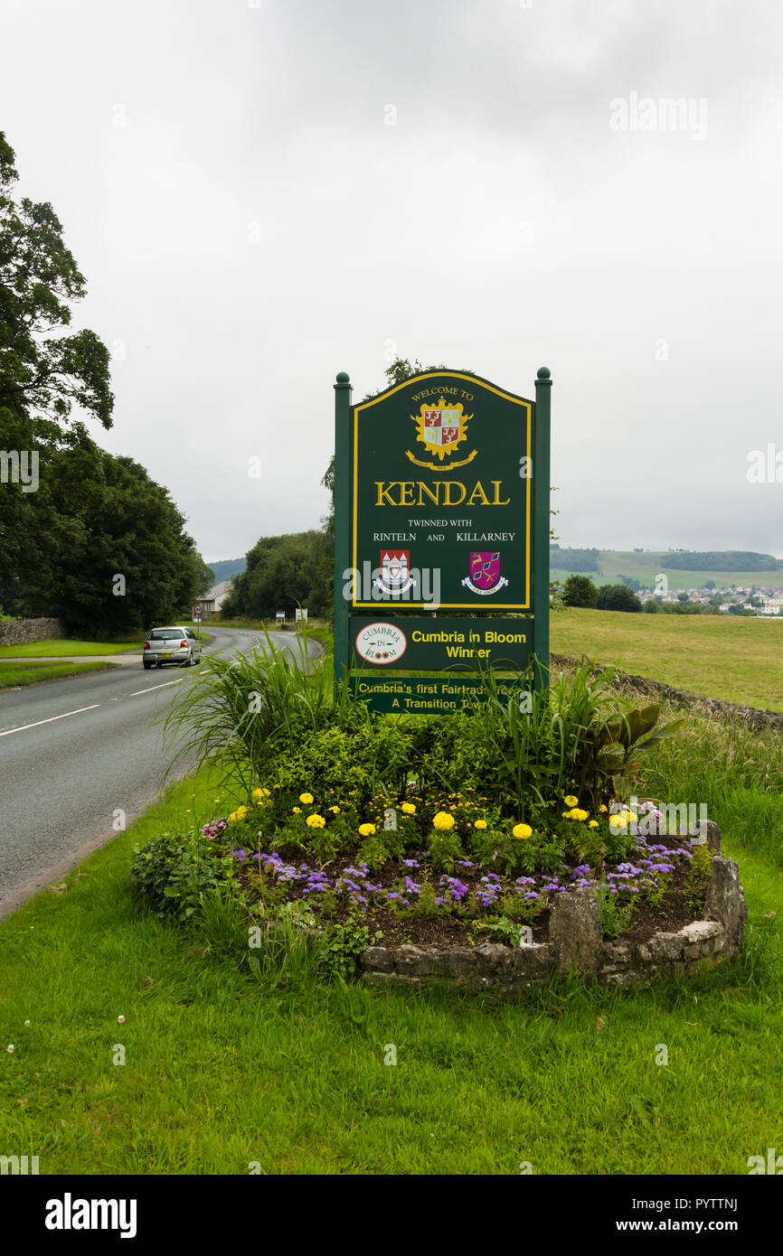 Welcome to Kendal sign and flowerbed on the A6 road, north east of Kendal. The sign highlights the town as winner of the Cumbria in Bloom competition. - Stock Image