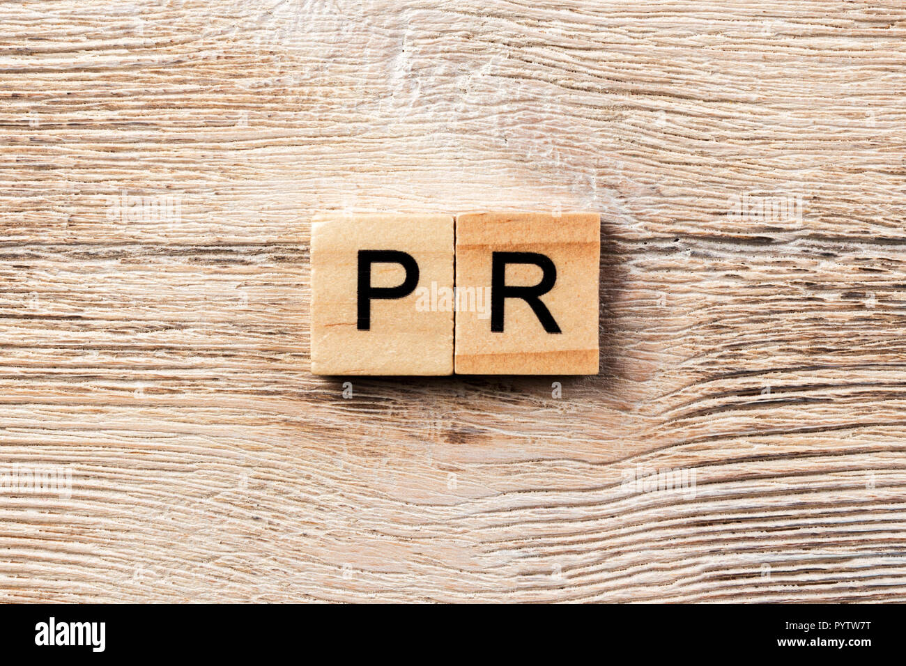 pr word written on wood block. public relation text on table, concept. Stock Photo