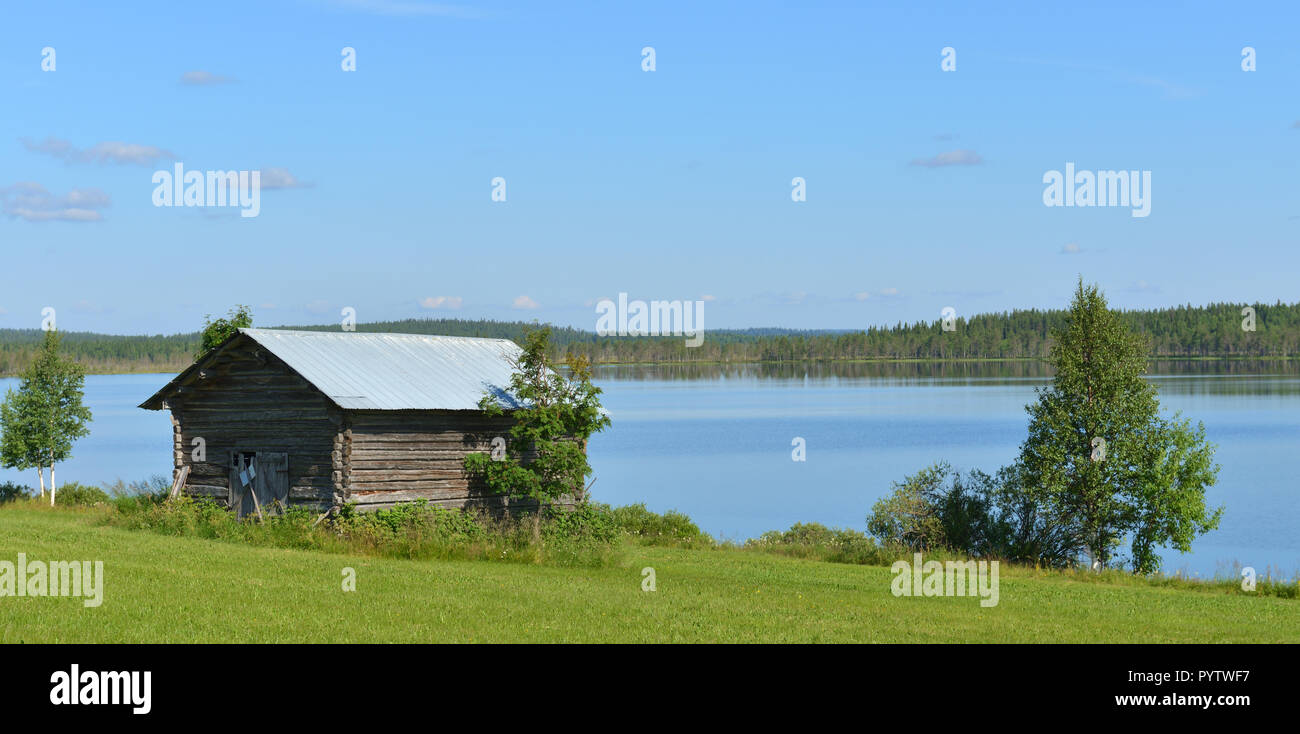 Summer northern landscape with barn on shore of forest lake. Finland, Lapland - Stock Image