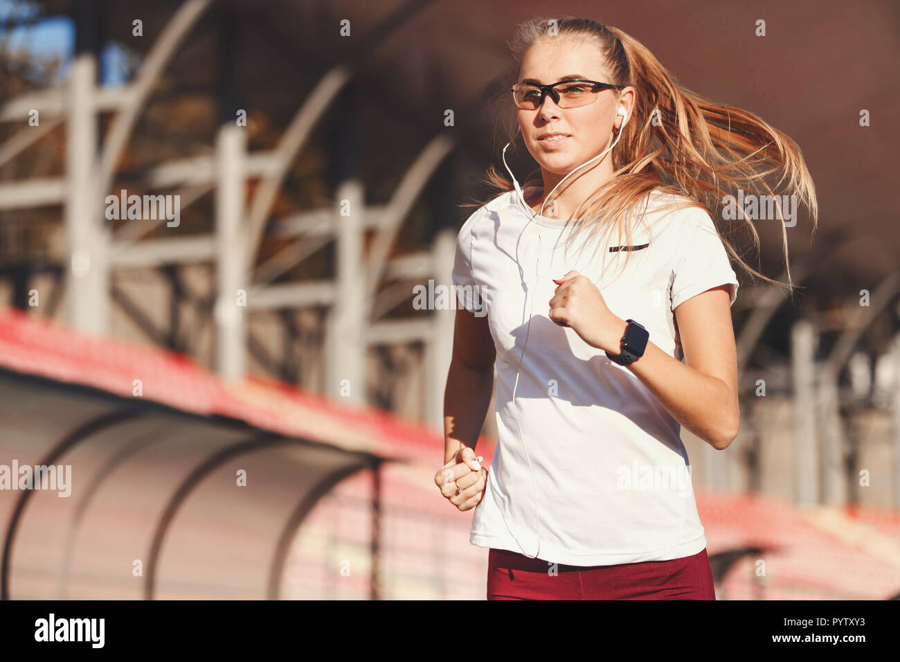 Fitness blonde long haired woman in sportswear jogging while listening music at the football stadium outdoor, healthy lifestyle and people concept - Stock Photo