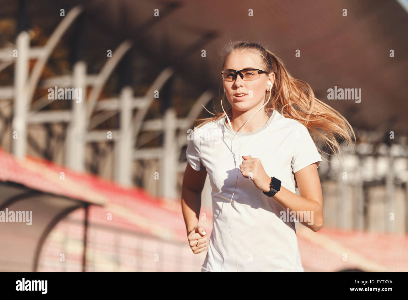 Fitness blonde long haired woman in sportswear listening music and running at the football stadium outdoor, healthy lifestyle and people concept - Stock Photo