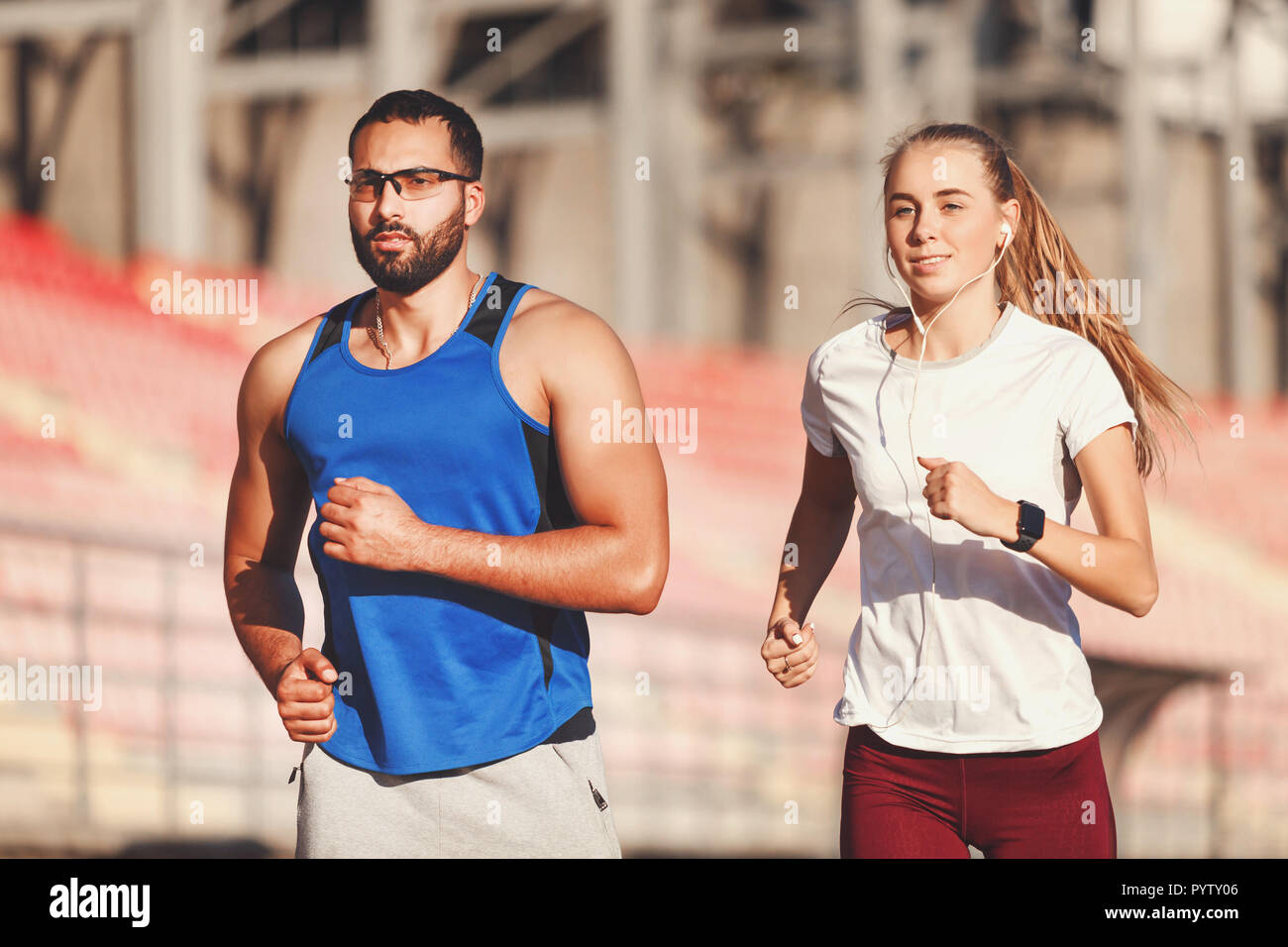 Sportish pretty blonde long haired woman in white t-shirt and multicultural handsome bearded man in blue shirt jogging at the football stadium outdoor, healthy lifestyle and people concept - Stock Photo