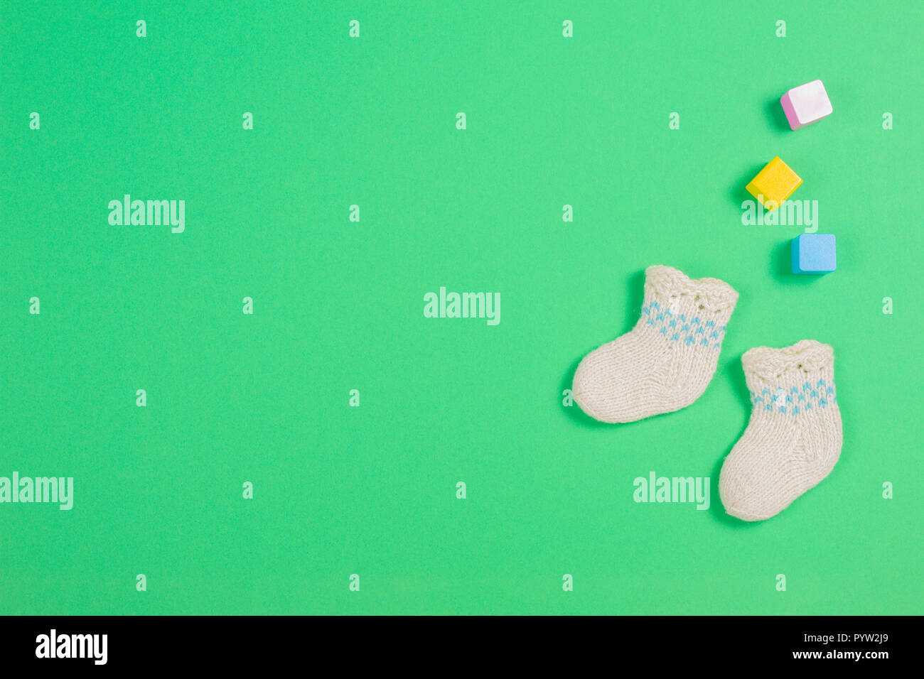 Knitted baby wool socks and wooden bricks on green background. - Stock Image