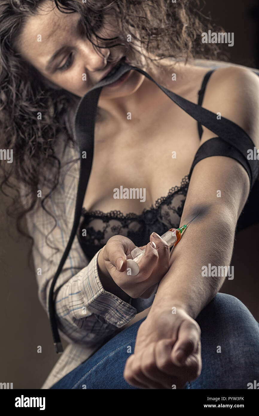 Drug addict young woman with syringe in action - Stock Image
