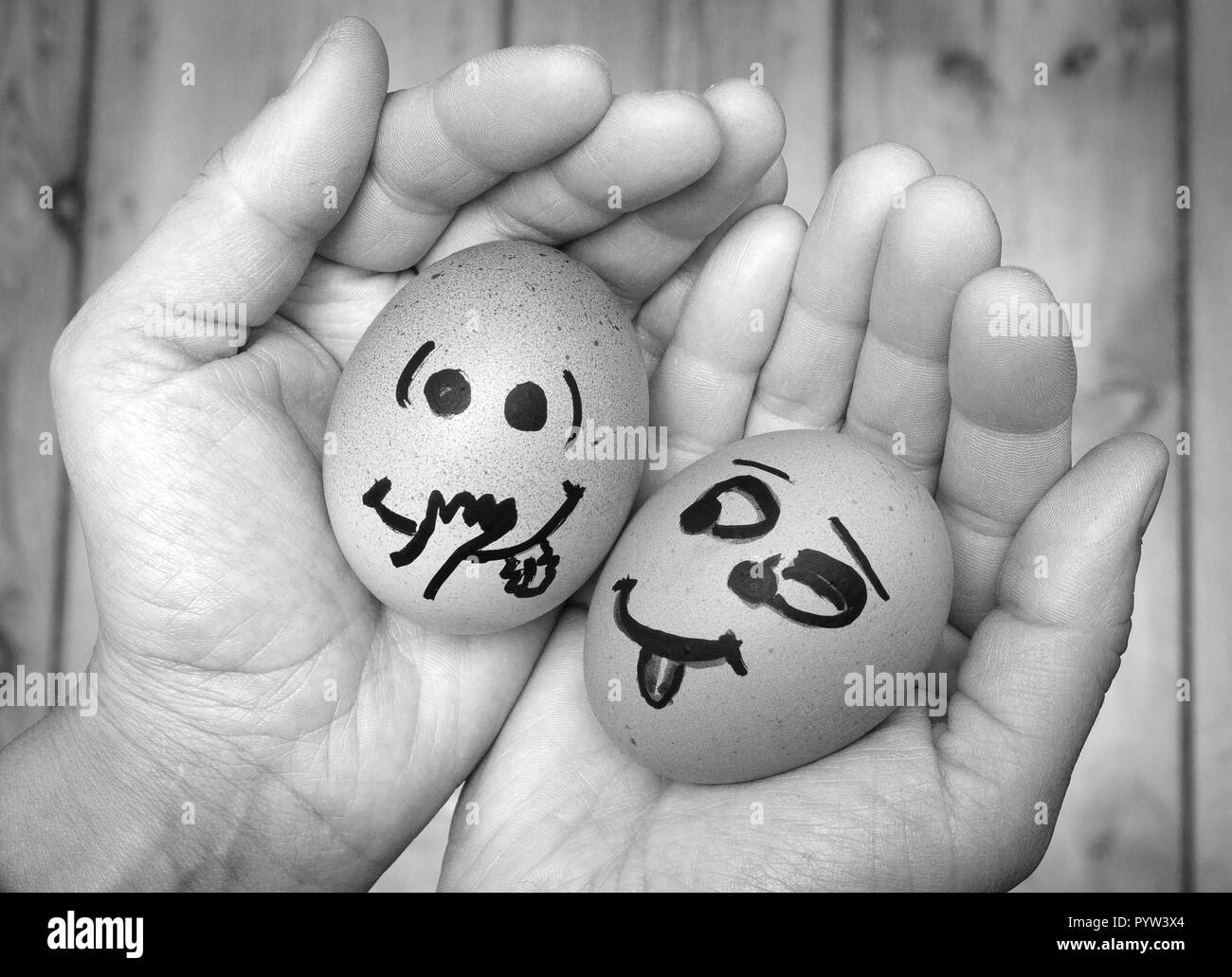 An egg staring lustfully, lecherously at another egg, both in female hands. Two eggs in love, being together, Eggs faces, drawnigs on eggs. - Stock Image