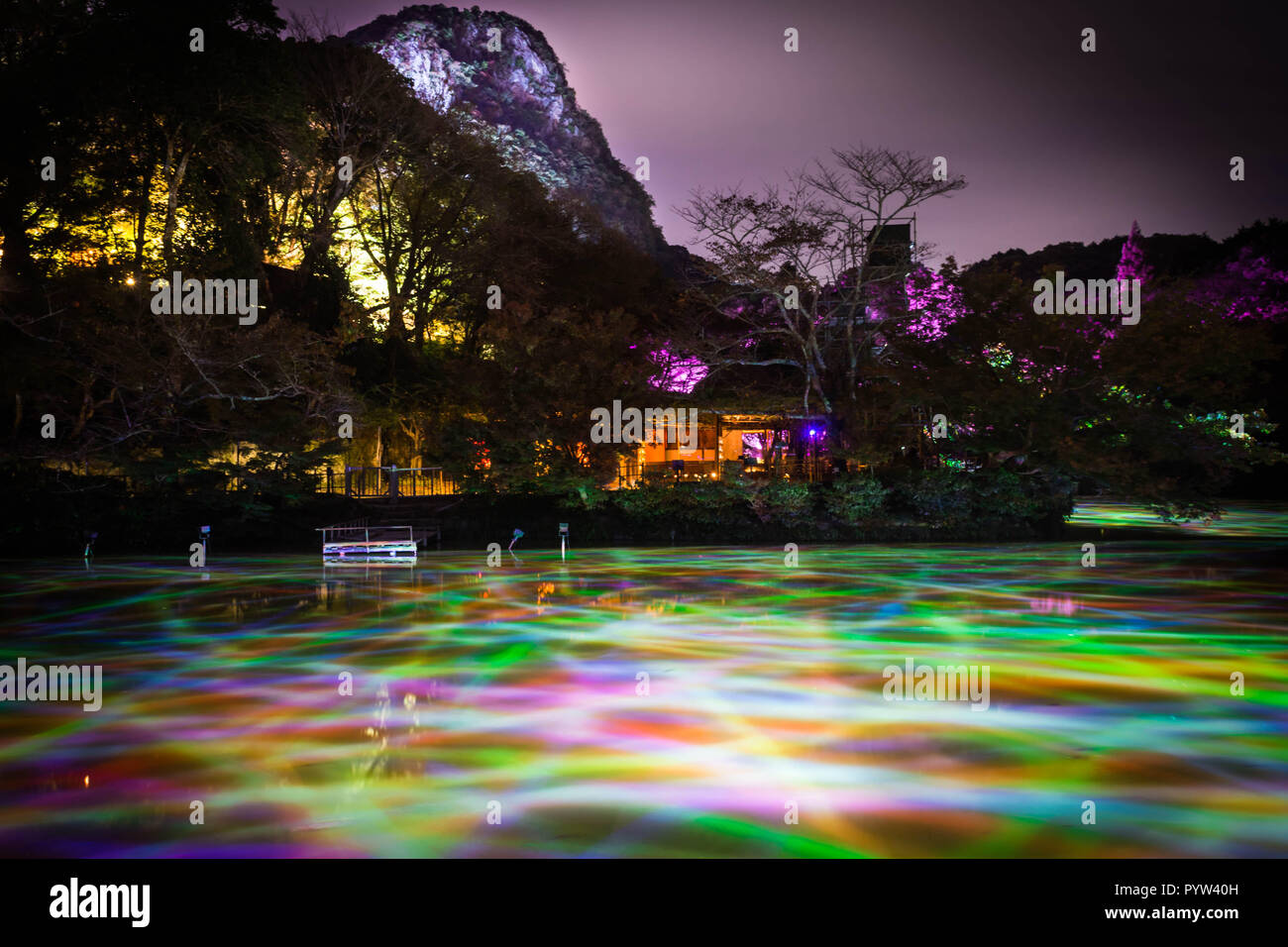 Different color of lights in the water pond at night at Mifuneyama Rakuen Garden in Saga, Japan. - Stock Image