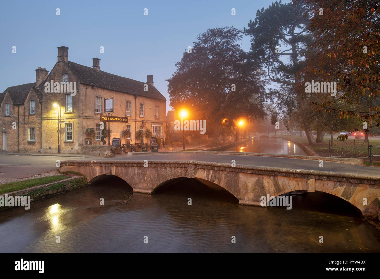 Mist and fog just after dawn in the cotswold village of Bourton on the Water in autumn. Bourton on the Water, Cotswolds, Gloucestershire, England Stock Photo