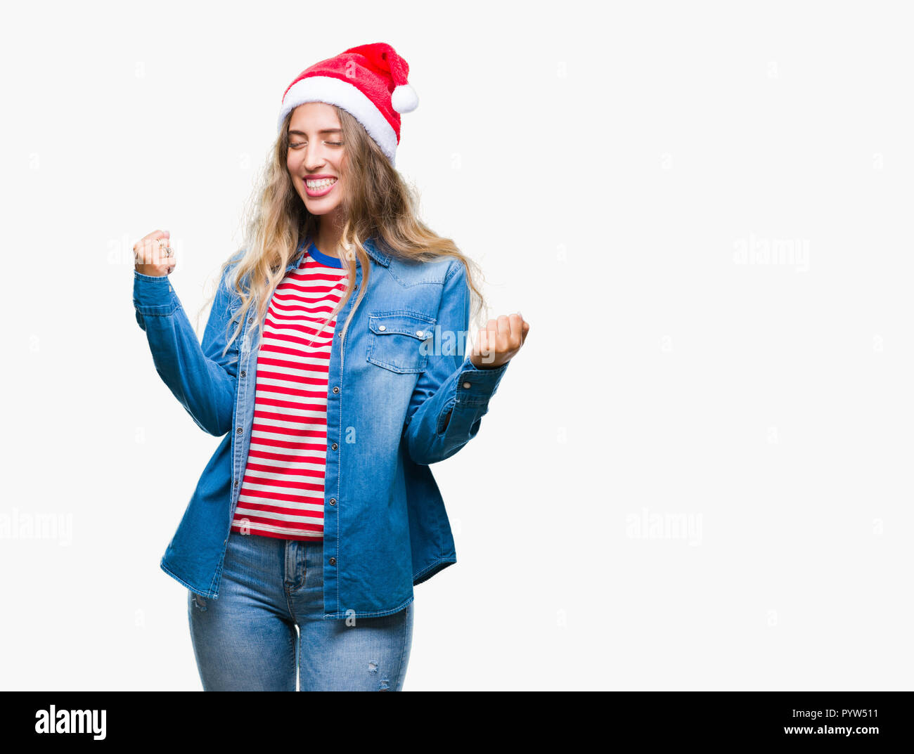 Beautiful young blonde woman wearing christmas hat over isolated background very happy and excited doing winner gesture with arms raised, smiling and  - Stock Image
