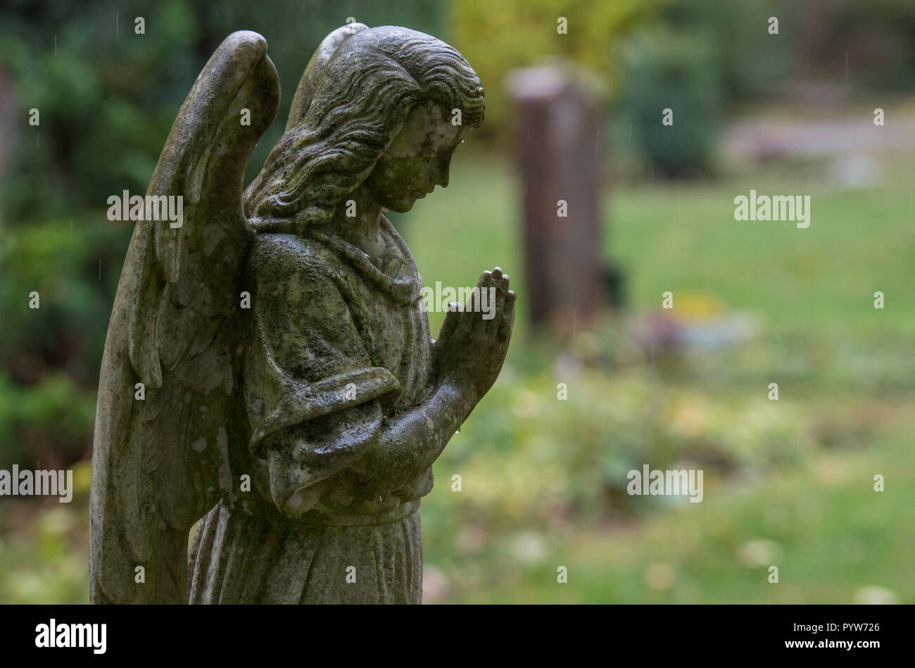 """30 October 2018, Hessen, Frankfurt/Main: An angel sculpture stands on a grave. In the cemeteries there are more and more graves that have been left to their own devices for years. The reasons for this are different. (Zu dpa """"Neglected graves - relatives extend more rarely"""" of 30.10.2018) Photo: Boris Roessler/dpa Stock Photo"""