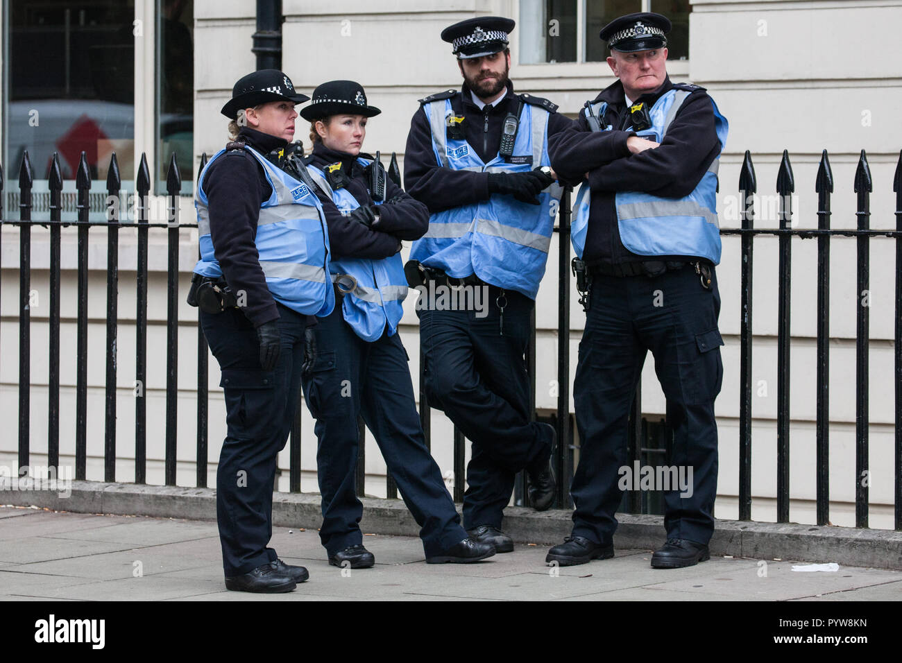 London, UK. 30th October, 2018. Police officers observe members and supporters of the Independent Workers of Great Britain (IWGB) trade union at a rally following a march with precarious workers from the offices of Transport for London to the University of London via the Court of Appeal in support of Uber drivers who are seeking employment rights. The Court of Appeal will today hear an appeal by Uber against a ruling that its drivers are employees rather than self-employed workers. Credit: Mark Kerrison/Alamy Live News - Stock Image
