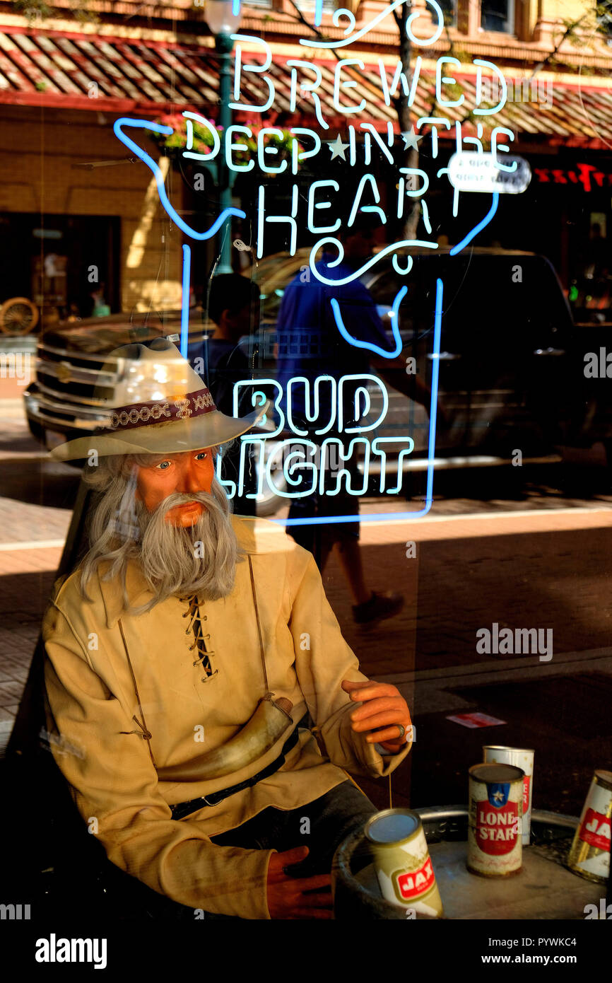 Window display at a bar in downtown San Antonio, Texas, USA; prospector or cowboy using a metal keg as a table with beer cans on top; neon Bud Light. - Stock Image