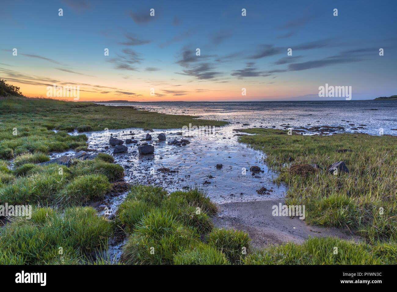 Tidal marsh Sea Inlet sunset at low tide near Waren mill, Northumberland, UK Stock Photo