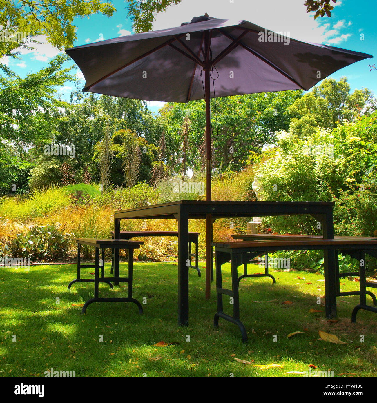 Dining Table With Chairs And Parasol In The Shade In A Lush Garden