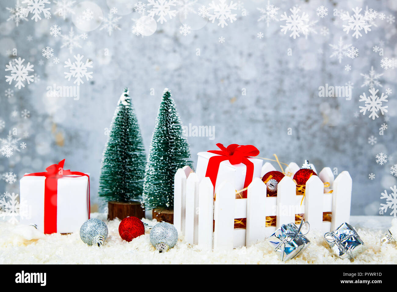 Christmas gifts and decorations in a white box on snow on a grunge ...