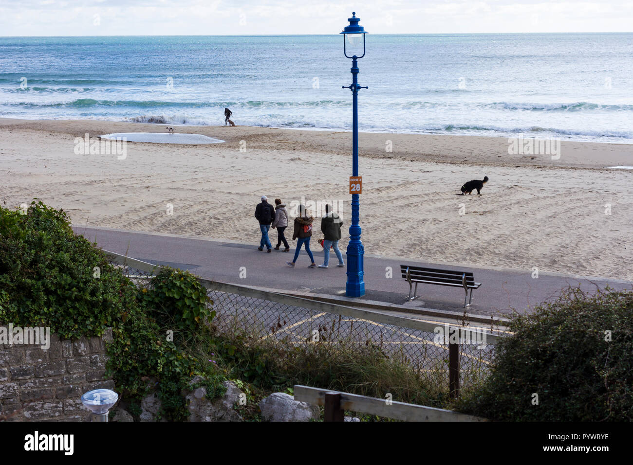 People & dogs out for a sunday afternoon walk along Bournemouth promenade & beach on a chilly day in October 2018, Dorset, UK - Stock Image
