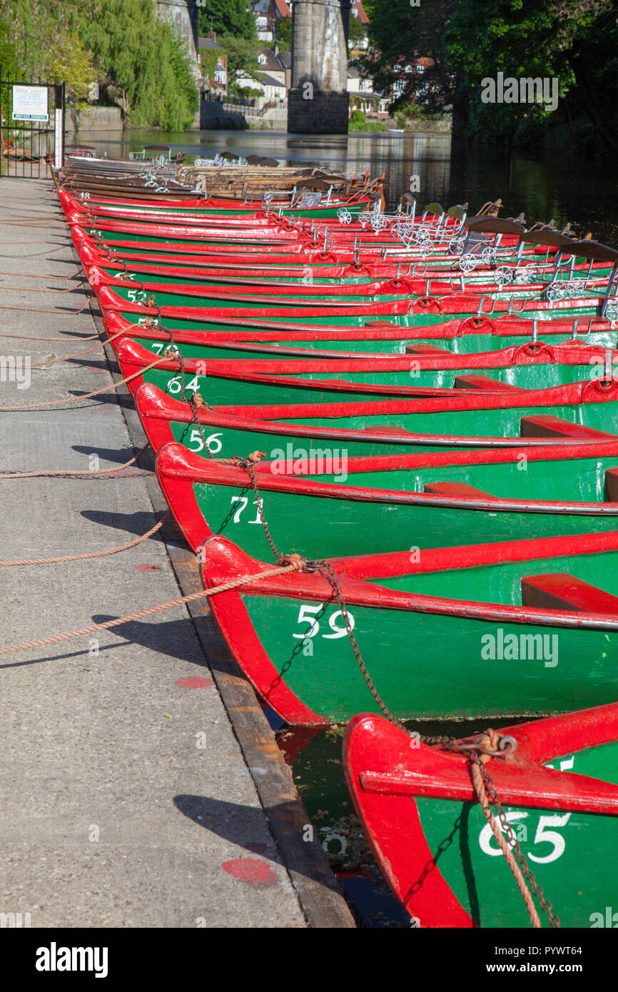 Green and red painted rowing boats lined up beside the River Nidd in Knaresborough, North Yorkshire waiting for visitors to take them out on the river - Stock Image