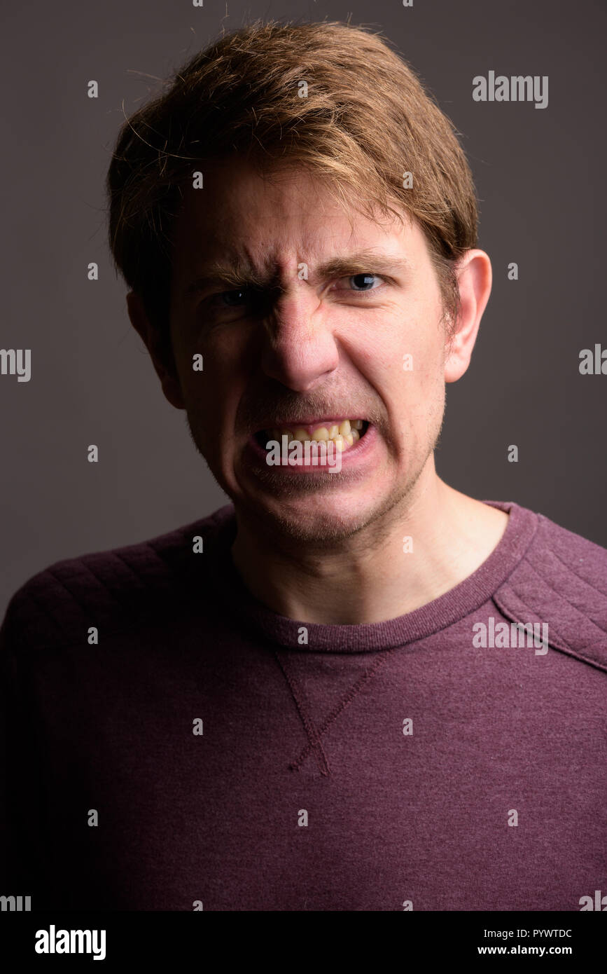 Portrait of handsome man against gray background - Stock Image