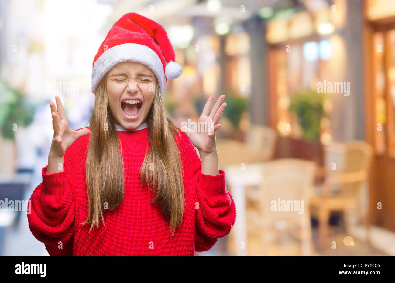 Crazy For Christmas.Young Beautiful Girl Wearing Christmas Hat Over Isolated
