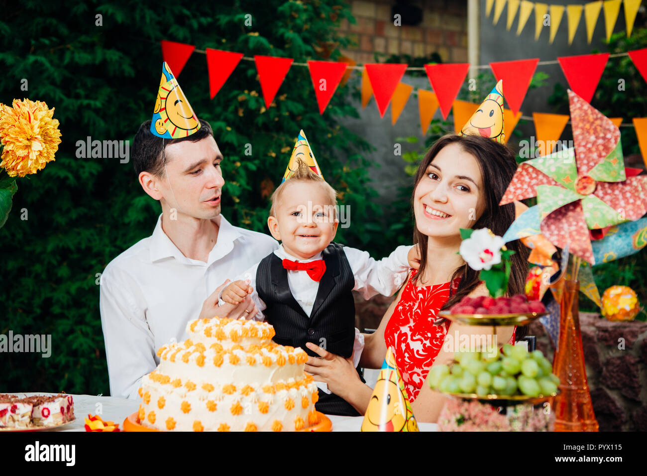 Children birthday theme. family of three Caucasian people sitting in backyard of the house at a festive decorated table in funny hats and caps on thei - Stock Image