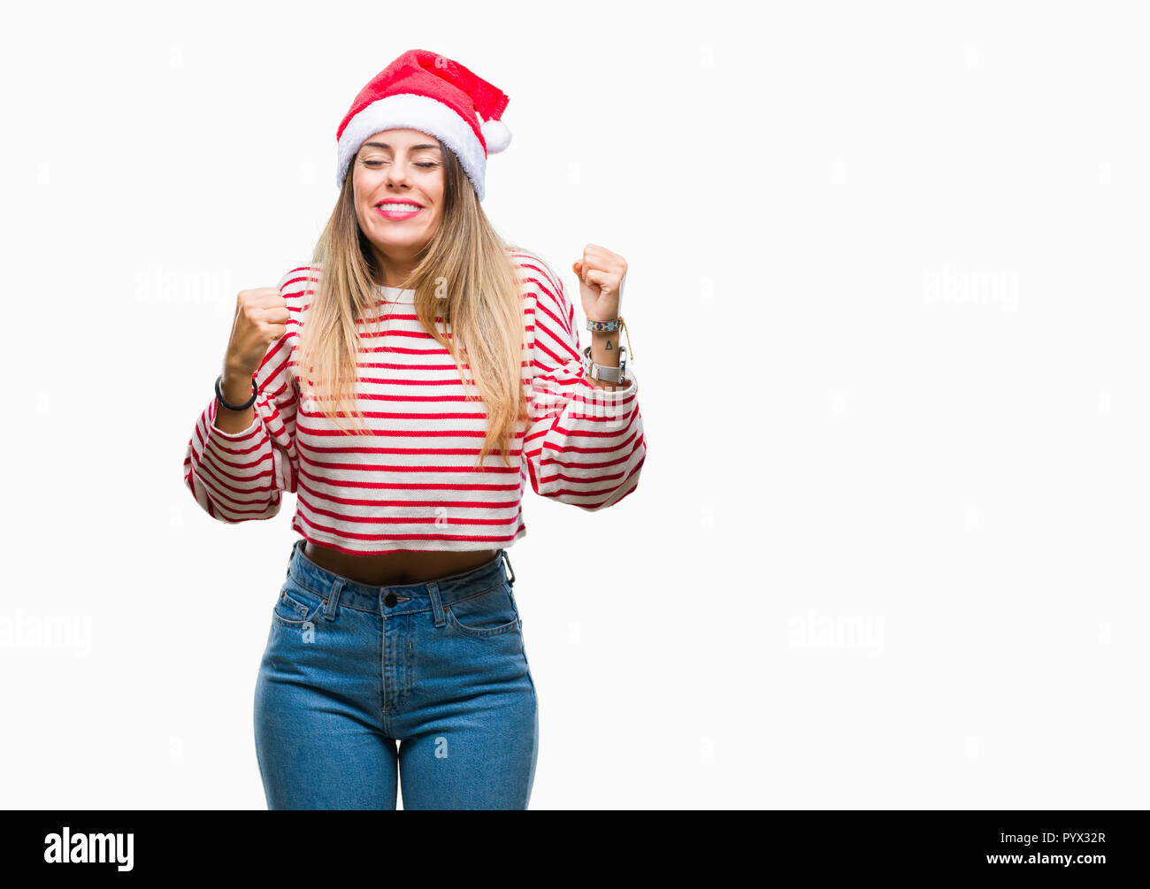 Young beautiful woman wearing christmas hat over isolated background very happy and excited doing winner gesture with arms raised, smiling and screami - Stock Image