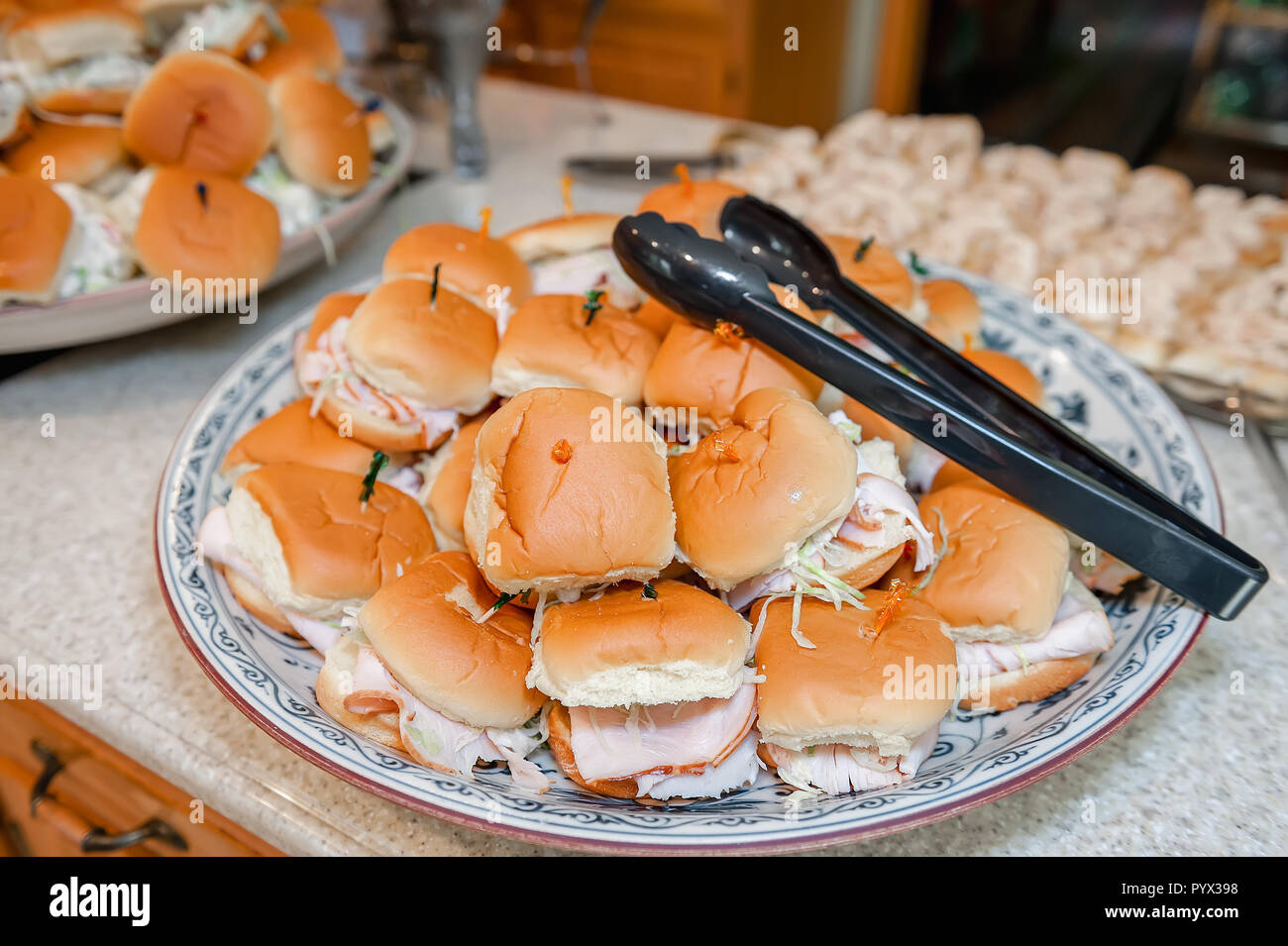 A pile of prepared turkey sandwiches stacked on a plate with tongs for serving. - Stock Image