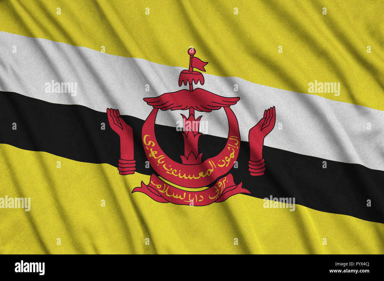 Brunei Darussalam flag  is depicted on a sports cloth fabric with many folds. Sport team waving banner - Stock Image