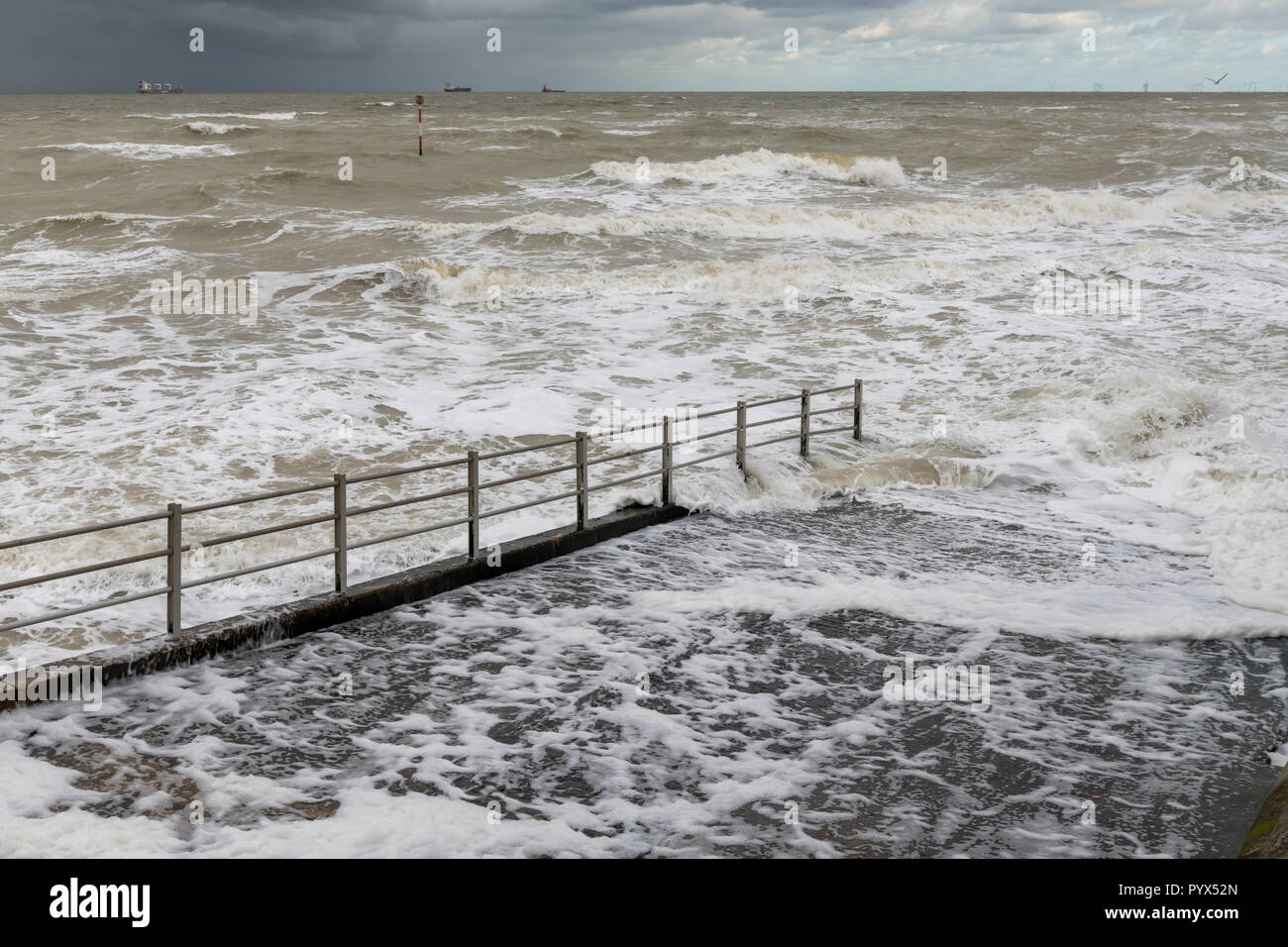 Margate jetty going down to the frightening rough sea. - Stock Image