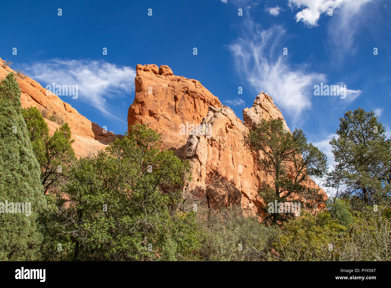 Garden of the Gods in Colorado Springs - huge red rock bluffs jut upwards against dramatic blue sky with whispy clouds Stock Photo