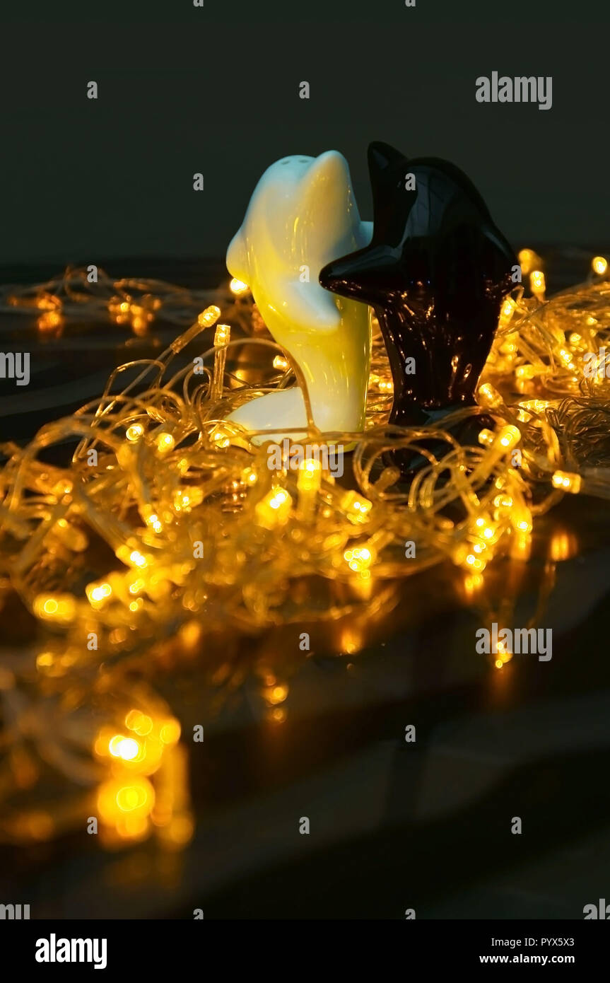 Salt shakers in the form of a black and white dolphin in bright Christmas lights - Stock Image