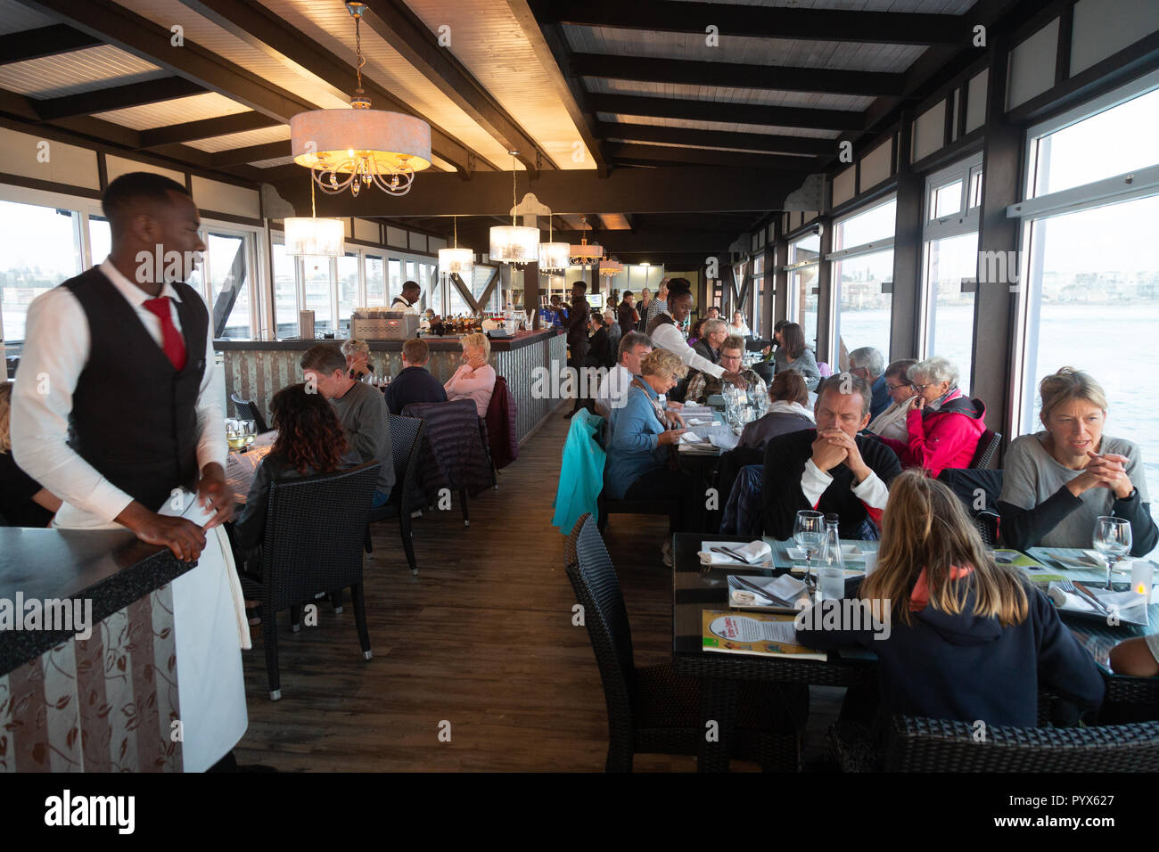 Swakopmund Namibia; people eating in the interior of The Jetty restaurant, Swakopmund, Namibia Africa - Stock Image