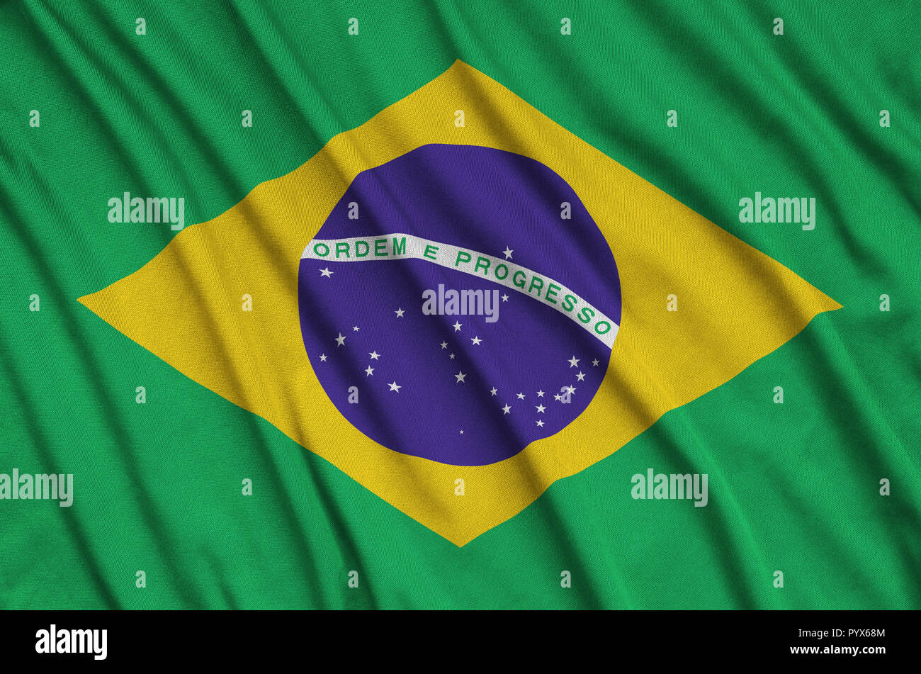 Brazil flag  is depicted on a sports cloth fabric with many folds. Sport team waving banner - Stock Image