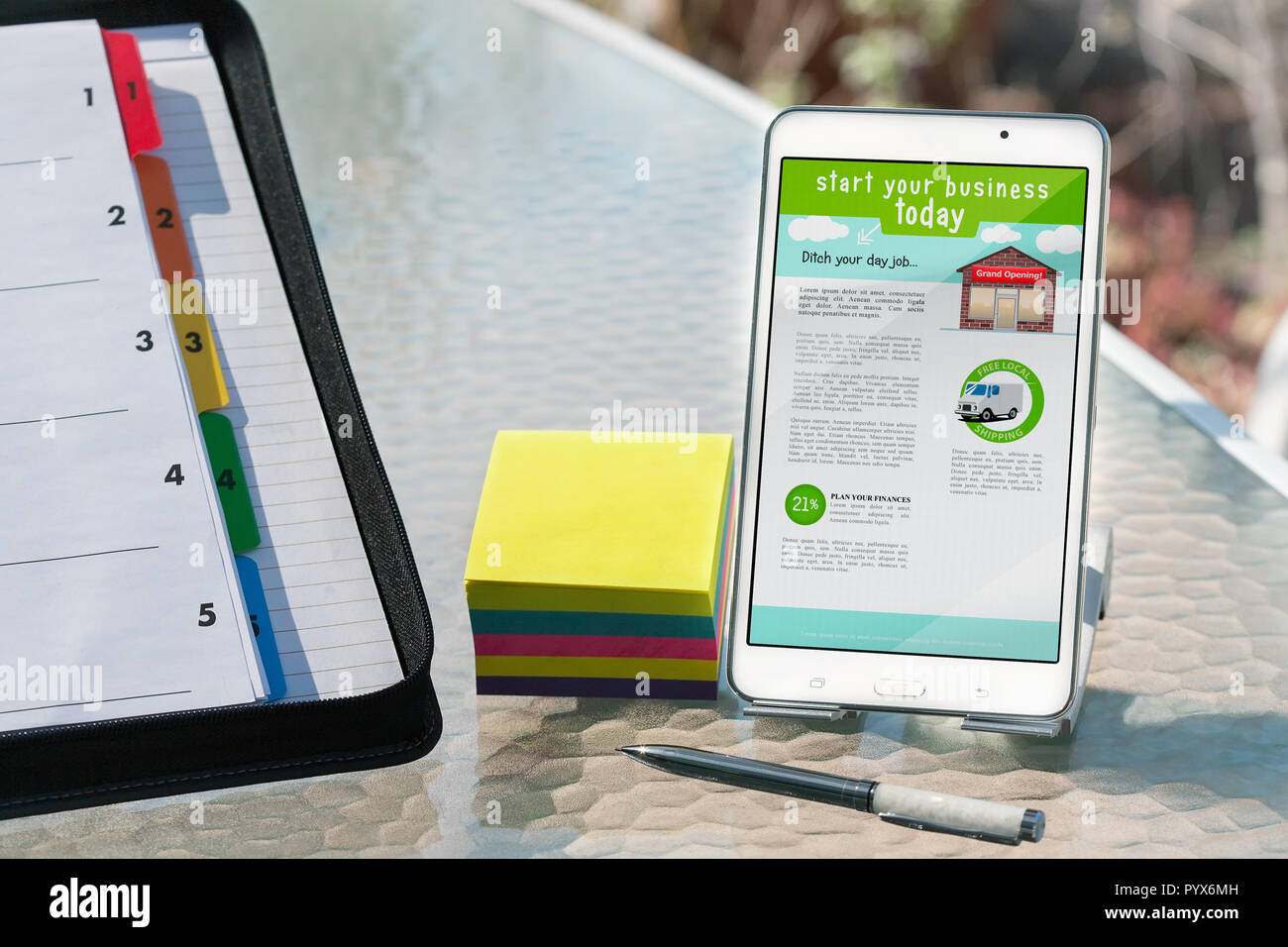 Business planning in outdoor setting with notes, scheduling folder and mobile phone with home based business information to get started today. - Stock Image