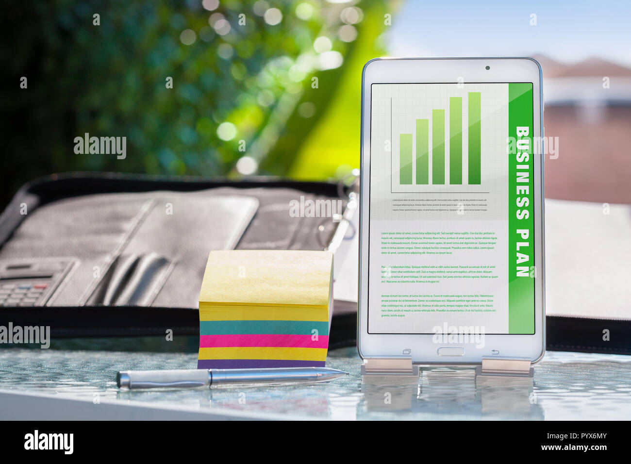Business plan presentation on a mobile device, phone or tablet with colorful notes, binder, and pen in outdoor meeting. - Stock Image