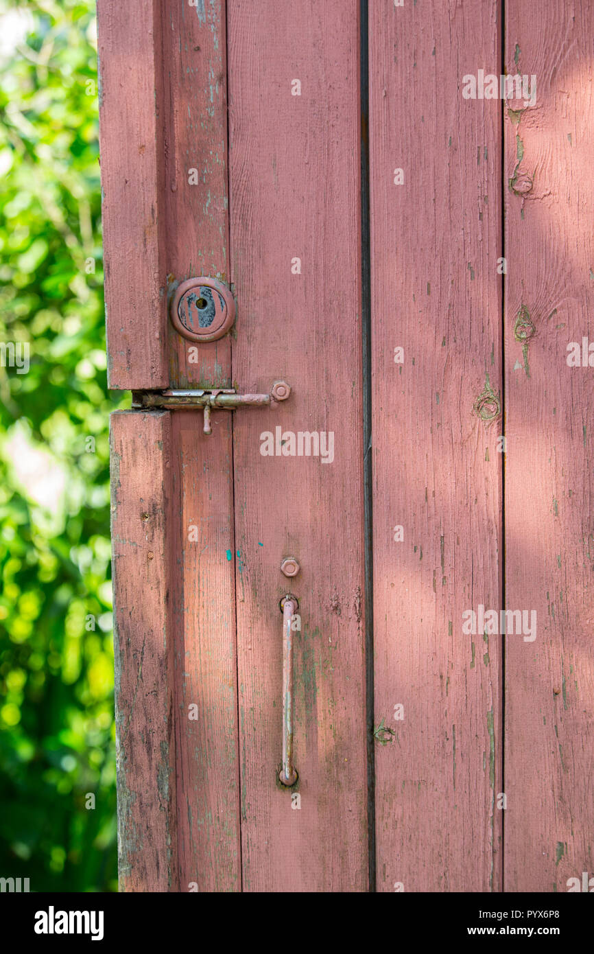 Painted wooden door of a country house. Old-fashioned latch and gate valve. Closeup. - Stock Image
