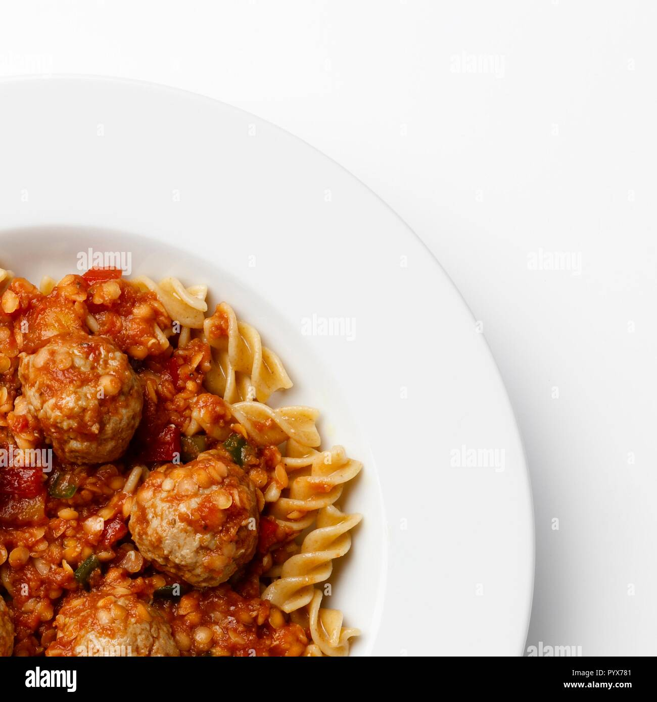 Corner of a plate of Meatballs in a tomato sause with paste twists, on a white background. Stock Photo