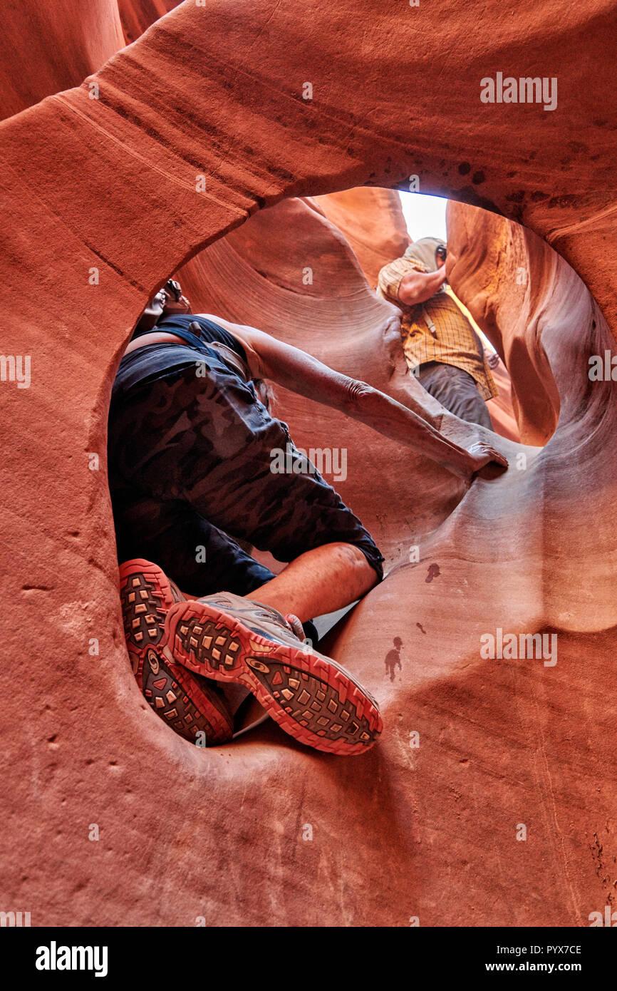 tourist squeeze through peekaboo slot canyon, Grand Staircase-Escalante National Monument, Utah, USA, North America Stock Photo