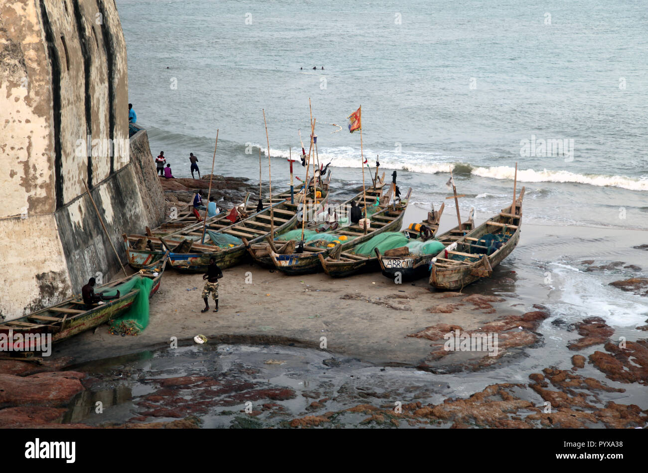 Fishermen and fishing boats at the base of Cape Coast Castle in Cape Coast, Ghana Stock Photo