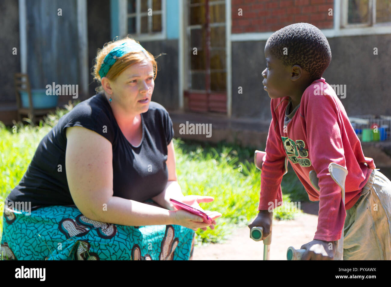 Uganda. 2017/4/28. A white-skinned missionary medical doctor (called 'mzungu' or 'muzungu' by the locals) delights in the progress her patient - a you - Stock Image